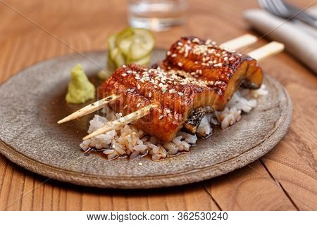 Fried unagi eel with barbecue sauce and rice close-up
