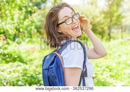 Happy Beautiful Positive Student Girl In Eyeglasses With Backpack Smiling On Green Park Background.
