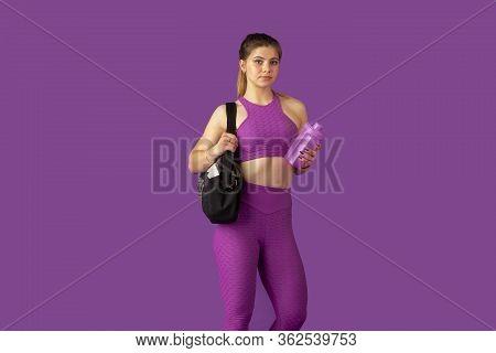 Beautiful Young Female Athlete Practicing In Studio, Monochrome Purple Portrait. Sportive Caucasian
