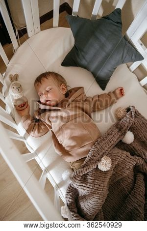 Cute Little 1-year-old Baby Is Lying On A Cot While Sleeping With Windows Of Light On His Face