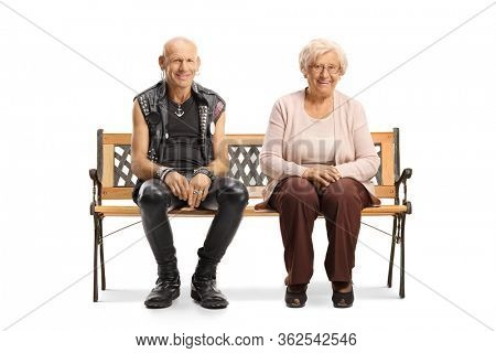 Bald punk with an elderly woman sitting on a bench and smiling at the camera isolated on white background