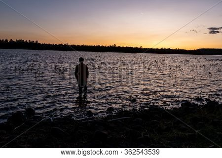 Solitary Figure Wading Into The Lake At Sunset