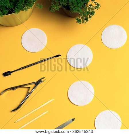 Equipment For Manicure And Pedicure On A Yellow Background. Tongs, Nail File, Pusher, Cotton Pads. H
