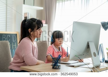 Asian Girl Student With Mother Video Conference E-learning With Teacher On Computer In Living Room A