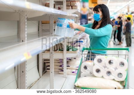 Asian Woman Looking At Supermarket Empty Drink Water Bottle Shelves Amid Covid-19 Coronavirus Fears,