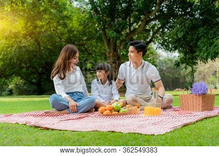 Asian Teen Family Happy Holiday Picnic Moment In The Park With Mother And Daughter Looking At Father