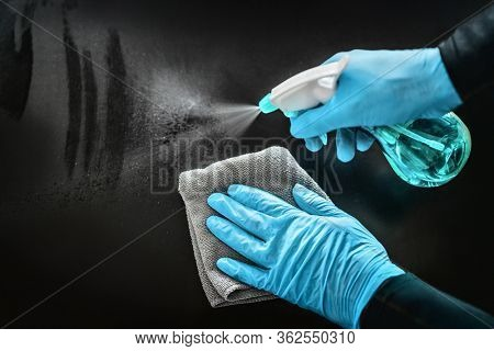Surface cleaning disinfecting home with sanitizing antibacterial wipes protection against COVID-19 spreading wearing medical blue gloves. Sanitize surfaces prevention in hospitals and public spaces.
