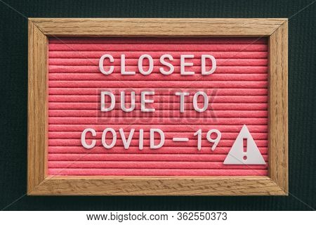 Coronavirus store closure sign. Closed due to COVID-19 message board for retail business COVID-19 pandemic outbreak. Government shutdown of restaurants, bakeries, non essential services. Pink letters.