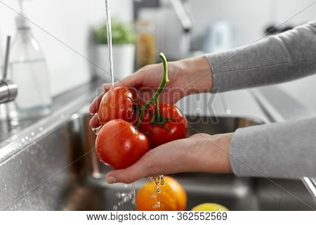 hygiene, health care and safety concept - close up of woman's hands washing fruits and vegetables in kitchen at home