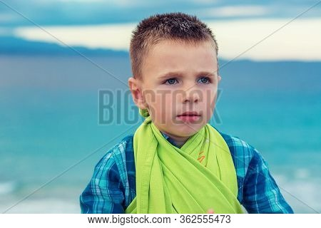 Closeup Portrait Of A Thoughtful Young Little Boy, Kid At The Beach Looking To The Side Pensive Dayd