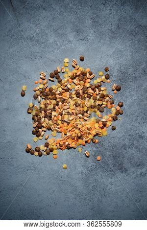 Mix of legumes and cereals on a stone table.