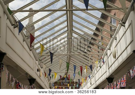 Colourful Bunting Flags In A Glass Roofed Walkway In An English Town.