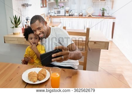 Happy African Father And Son Taking Selfie Photo With Smartphone During Lunch Time In Dining And Kit