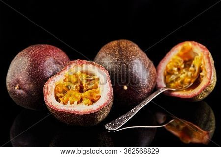Passiflora Is Cut Into Two Halves With A Spoon Inside And Two Whole Isolated On A Black Background.