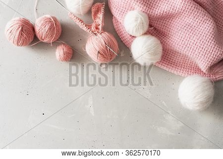 Incomplete Knitting Project With Wooden Needles. Light Background, Pink Threads.