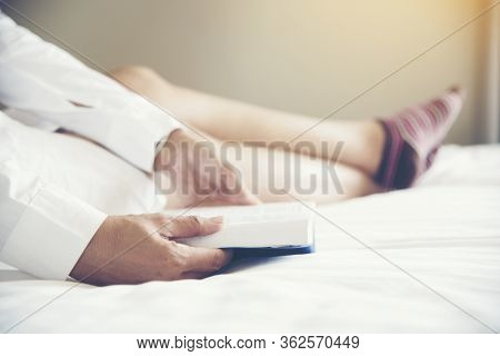 Woman Reader Who Love Reading Book While Sitting On Bed With Comfortable And Relax. Leisure Time Con