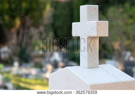 White Stone Cross With Green Orange Marks Worn Over Time Marking A Tombstone In A Graveyard