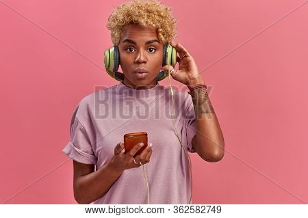 Impressed Shocked Dark Skinned Hipster Female Surprised To Listen Audio Track With High Volume, Has