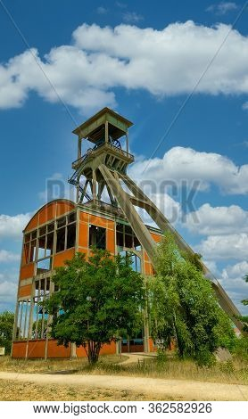 A Disused Coal Mine Pithead Winding Gear Of An Old Belgian Coal Mine Shaft Against A Clear Blue Sky