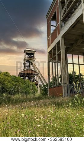 A Disused Coal Mine Pithead Winding Gear Of An Old Belgian Coal Mine Shaft Against A Dramatic Sunset