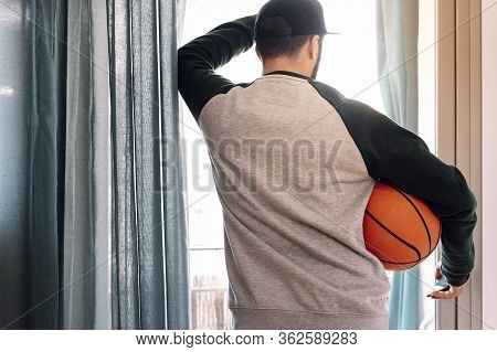 Man Confined Looking Out His Window With A Basketball, Concept Of Quarantine And Confinement