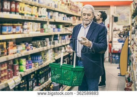 Mature Man Shopping In Grocery Store. Serious Man Holding Shopping Basket And Choosing Goods In Supe