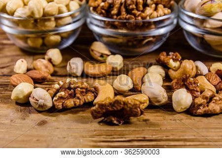 Various Nuts (almond, Cashew, Hazelnut, Pistachio, Walnut) In Glass Bowls On Wooden Table. Vegetaria