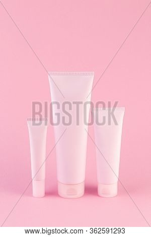 Collection Of Three Cosmetic Tubes On Pastel Pink Background. Plastic Tube With Face Or Body Cream O