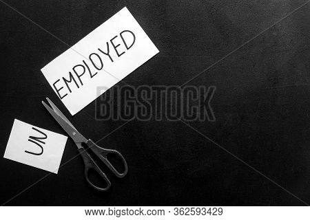 Employment, New Job Concept. Torn Paper Sheet - Unemployed - Sciccors On Black Table Top-down