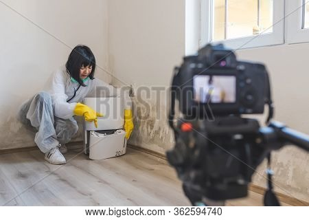 Video Camera Filming How Woman Consultant Explains How Dehumidifier Collect Water From Air Inside Of