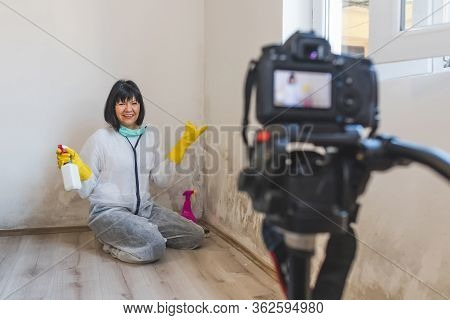 Video Camera Filming Woman Removes Mold From Wall Using Spray Bottle With Mold Removal Products.