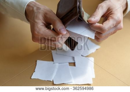 Side View Of A Man Shaking Pieces Of Paper From An Empty Wallet On A Light Monophonic Background. Ba