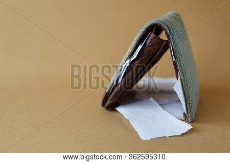 Side View Of An Empty Wallet With Pieces Of Paper Instead Of Money On A Light Monophonic Background.