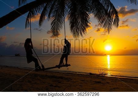 Silhouetted Couple In Love Walks On The Beach During Sunset. Riding On A Swing Tied To A Palm Tree A