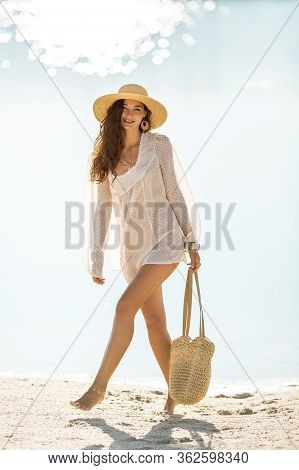 Romantic Woman Walking On A Beach Against A Beautiful Sea Bokeh Background. Tanned Girl In Fashionab