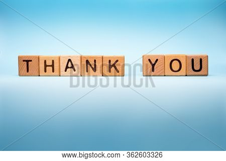 Thank You Background. Word Thank You Made With Wooden Cubes On Blue Background. Message Of Gratitude