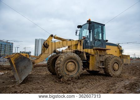 Front-end Loader Working At Construction Site. Earth-moving Heavy Equipment For Road Work. Public Wo