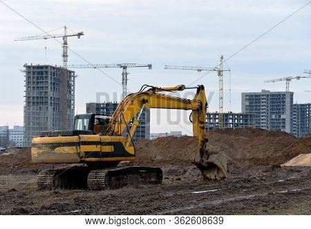 Yellow Excavator During Groundwork On Construction Site. Hydraulic Backhoe On Earthworks. Heavy Equi