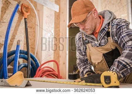 Male Carpenter Measuring Wood Board For Cutting.