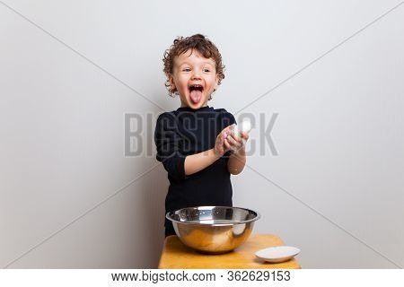 Funny Baby Washes Hands With Soap In A Bowl Of Water. Kinky Screaming Boy In A Black Jacket Lathers