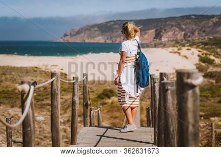 Adult Female Tourist Enjoying Costal View Of Praia Do Guincho Beach. Cascais, Portugal. This Is Popu