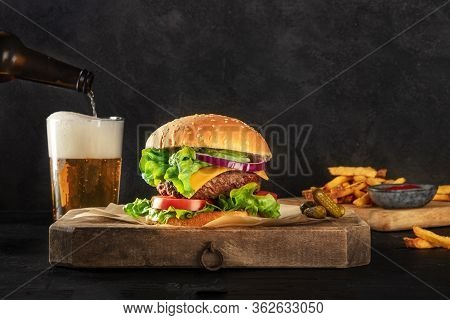 Burger And Beer. Hamburger With Beef, Cheese, Onion, Tomato, And Green Salad, A Side View On A Dark