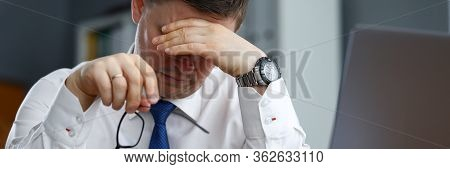 Tired Male Office Worker Sitting At Table Resting. Body Is Not Able To Function Without Proper Rest,