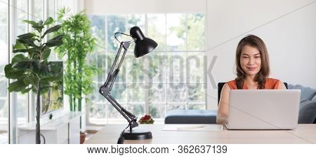 Beautiful Middle Age Asian Businesswoman Sitting At Desk And Using Laptop Notebook Computer In Apart