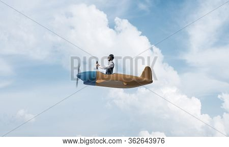 Young Man In Aviator Hat With Goggles Driving Propeller Plane. Traveling Around The World By Airplan