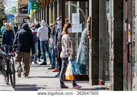 Uzhgorod, Ukraine - April 11, 2020: People In Medical Masks Standing In Line For Food Outside The Sh