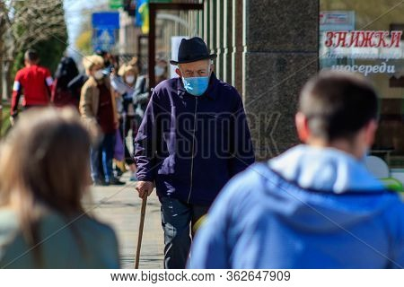 Uzhgorod, Ukraine - April 11, 2020: People Of Different Ages In Medical Masks Pass Near The Store Du