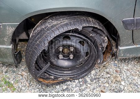 Destroyed Blown Out Tire With Exploded, Shredded And Damaged Tire On A Modern Automobile. Damaged Tr