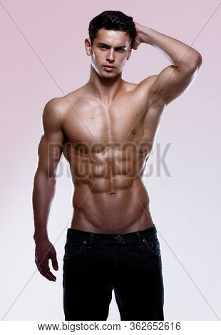 Portrait Of An Athletic Young Man With Shirtless Torso, Holding Hand Behind Head, Wear In Jeans, Ove