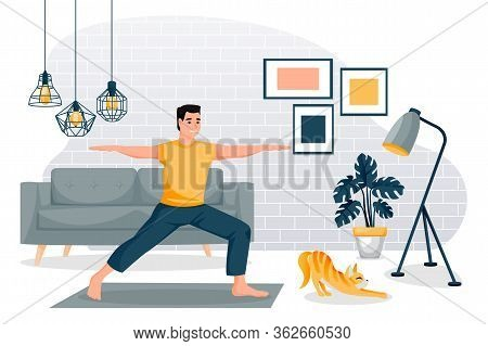 Guy Stands In A Warrior Pose Virabhadrasana. Home Yoga Exercise Practice. Man And Red Cute Cat Train